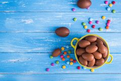 Full bowl of Easter chocolate eggs. With color dragee on  a wooden background Royalty Free Stock Images