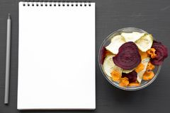 Full bowl of veggie chips, blank notepad and pencil on black table, top view. From above, overhead, flat lay. stock image