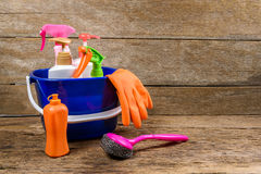 Full box of cleaning supplies and gloves on wooden background Royalty Free Stock Photos