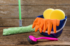 Full box of cleaning supplies, mop and gloves on wooden backgrou Stock Images
