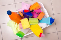 Full box of cleaning supplies on tiled floor Stock Image