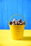 Full bucket of fresh quail eggs in the shell on a yellow surface Royalty Free Stock Photo