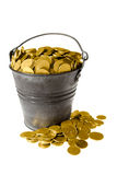 Full bucket of golden coins. Old zinc bucket with golden coins. Isolated stock photography