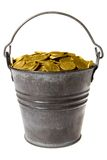Full bucket of golden coins. Old zinc bucket with golden coins. Isolated stock photos