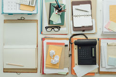Full business desktop. With piles of paperwork and objects, business productivity and work organization concept Royalty Free Stock Images