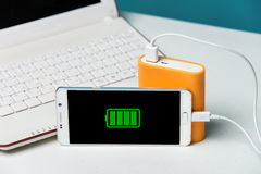 Full charge of a smartphone on its monitor with the cable connec Royalty Free Stock Photography