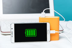 Full charge of a smartphone on its monitor with the cable connected to the special power bank. Modern laptop in the background Stock Photo