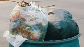 Full clogged trash can with plastic bags leftovers of food and other waste on a busy street on which cars and. A full clogged trash can with plastic bags stock footage