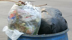Full clogged trash can with plastic bags leftovers of food and other waste on a busy street on which cars and. A full clogged trash can with plastic bags stock video footage