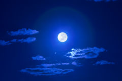 Full Clouds Moon Sky. A full moon glowing in a night sky with a few clouds Stock Image