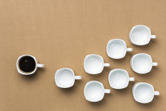 Full coffee cup followed by empty cups Royalty Free Stock Photography