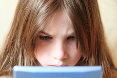 Full concentration. Girl concentrating on playing a pocket computer game Royalty Free Stock Images