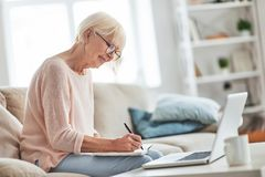 Full concentration. Beautiful senior woman writing something down while sitting on the couch at home royalty free stock image