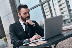 Full concentration. Good looking young man in full suit using computer and keeping hand on chin while sitting in the cafe outdoors stock photo