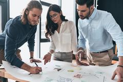 Full concentration. Group of young confident business people working together while man writing on blueprint in the office. Full concentration. Group of young stock image
