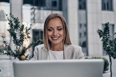Full concentration at work. Beautiful young woman using laptop and smiling while working indoors stock photo
