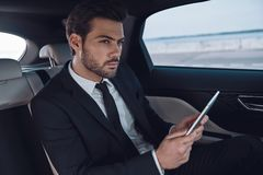 Full concentration at work. Handsome young man in full suit working using digital tablet while sitting in the car royalty free stock images