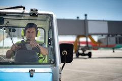 Male worker driving vehicle at airport terminal. Full concentration on work. Man in headphones with microphone driving car. He is holding the steering wheel and royalty free stock photos