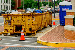 Full construction dumpster. Construction dumpster full of debris and a portable toilet on the street of a construction area Stock Photos