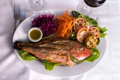 Full Cooked Tilapia Served with Vegetables and Fish Sauce Compli. Full cooked tilapia fish served in a plate with vegetables and fish sauce complimented with red royalty free stock images