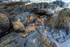 Full of crude oil on stone on oil spill accident Royalty Free Stock Photography