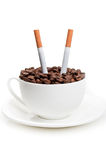 Full cup with coffee beans and cigarettes Stock Image