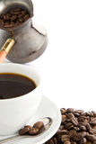 Full cup of coffee and pot on beans Royalty Free Stock Image