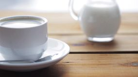 Full cup of coffee on wooden table stock video