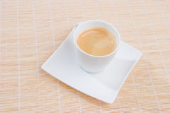 A full cup of espresso. On a white square saucer Royalty Free Stock Photography