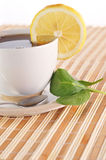 Full cup of tea with lemon Stock Image