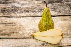 Full and cut in half pear fruit on wooden background. Royalty Free Stock Photos