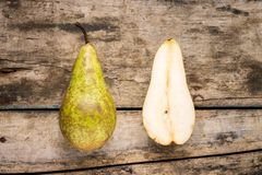 Full and cut in half pear fruit on wooden background. Royalty Free Stock Image