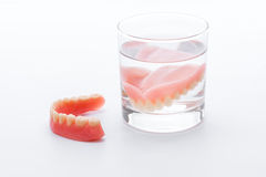 Full Denture in glass of water on white background.  Royalty Free Stock Photography
