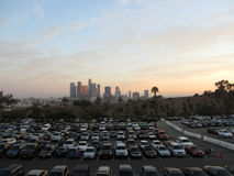 Full Dodger parking lot and  Downtown LA in the distance at Dusk. LA - JULY 13: Full Dodger parking lot and  Downtown LA in the distance at Dusk seen behind a Royalty Free Stock Photography