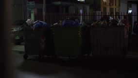 Full dumpsters in the street of small town, night view. NEA KALLIKRATIA, GREECE - AUGUST 12, 2017: Girl throwing a packet of garbage into to the full dumpsters stock footage