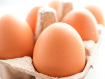 Full of eggs in paper basket. On white background Royalty Free Stock Photos
