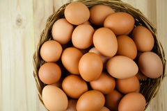 Full of Eggs put in a wicker basket in wooden background. Full of Eggs put in a wicker basket in wooden background Stock Image