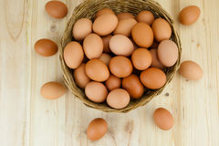 Full of Eggs put in a wicker basket in wooden background. Royalty Free Stock Image