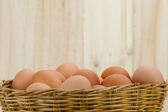 Full of Eggs put in a wicker basket in wooden background Royalty Free Stock Photos