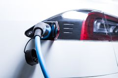 Full electric Tesla car charging picture. With plug-in connector as renewable energy green fuel stations concept Stock Photos