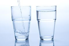 A full and a empty glass of water Stock Photos