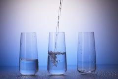 Full en tredjedel, halva-fyllda tomma dricka exponeringsglas, vatten Royaltyfria Bilder