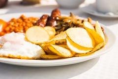 Full engelsk frukost inklusive korvar, tomater och champinjoner, ägg, bacon, vita bönor i tomatsås och chiper royaltyfria foton
