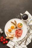 Full engelsk frukost på den vita plattan, svart bakgrund arkivbilder