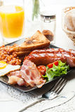 Full English breakfast with bacon, sausage, egg, baked beans and Stock Photos