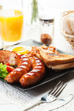 Full English breakfast with bacon, sausage, egg, baked beans and Royalty Free Stock Image