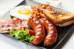 Full English breakfast with bacon, sausage, egg, baked beans and orange juice Royalty Free Stock Photography