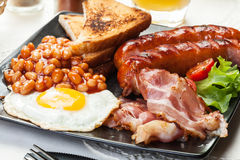 Full English breakfast with bacon, sausage, egg, baked beans and orange juice Royalty Free Stock Photos