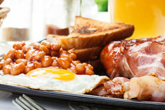 Full English breakfast with bacon, sausage, egg, baked beans and orange juice Stock Images