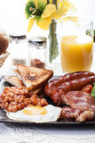 Full English breakfast with bacon, sausage, egg, baked beans and orange juice Stock Photography